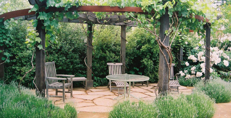 Patio area with masonry floor under a wood and iron awning